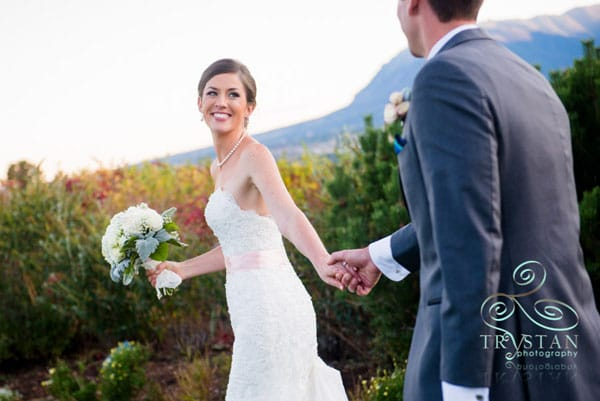 A photograph of a bride looking back over her shoulder and smiling at the groom as they walk away while holding hands.