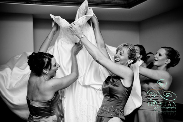 A photograph of a bride's mom and her bridesmaids laughing as they try to get her into the wedding dress.