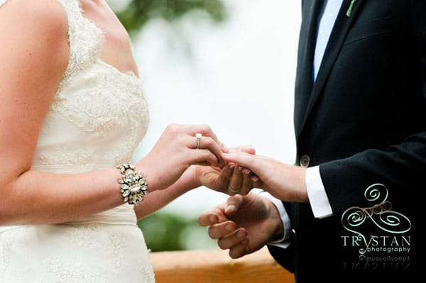 A photograph of a bride's hands as she places the wedding ring on the groom's hand during a wedding ceremony.