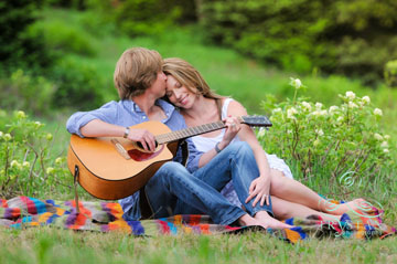 A portrait of a couple cuddling together in a lush green field, she is smiling and resting her head on his shoulder while he is playing guitar.
