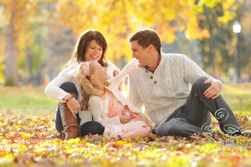 A portrait of a family laughing together while sitting in fallen leaves in Autumn in Colorado Springs.