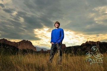 A portrait of a young male high school senior standing confidently in a field with The Garden of the Gods and stunning sunset skies behind him.
