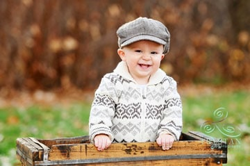 A portrait of a little boy in an adorable paper-boy hat and sweater laughing in an antique crate in a park in Autumn in Colorado Springs..
