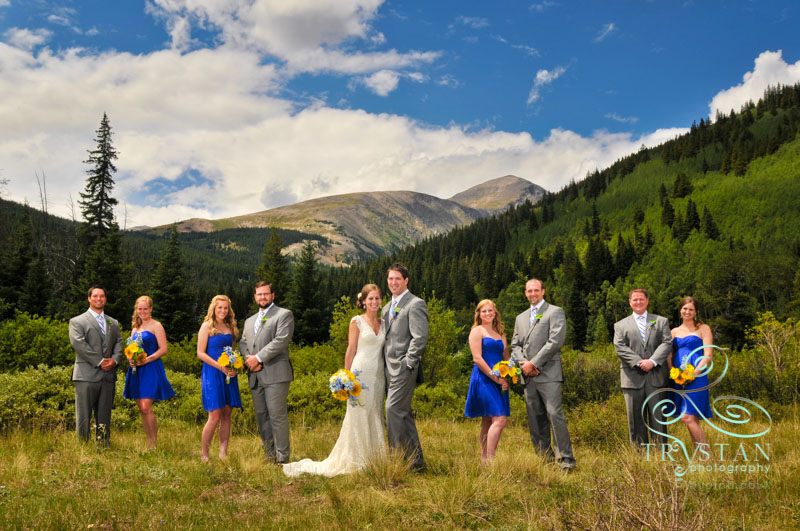 A photography of a wedding party standing in a valley in Blue River outside Breckenridge with the peak of Mt. Quandary looming behind them..