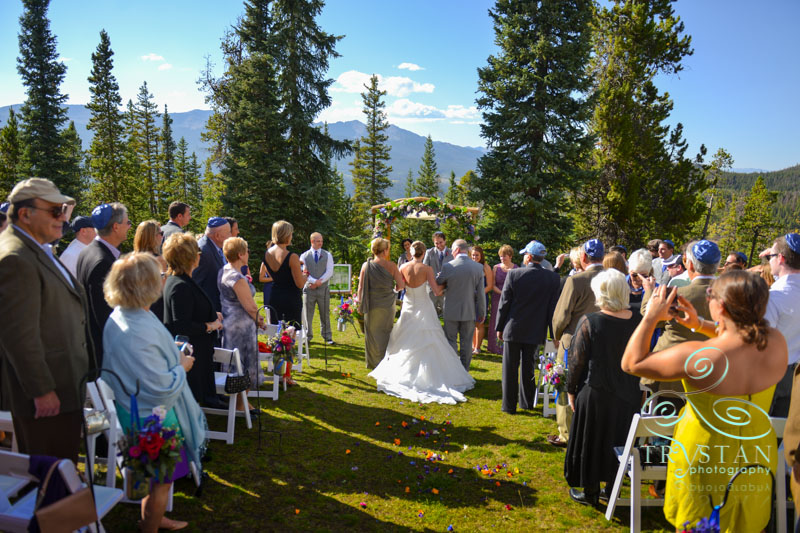 A photography of a bride being walked down the aisle by her mother and father at a wedding ceremony at V3 Ranch in Breckenridge, Colorado.