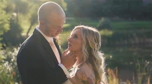 A wedding video still of a groom tenderly touching the bride's face in gorgeous streaming sunlight with a lake behind.