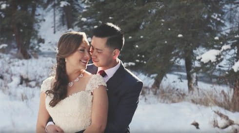 A wedding video still of a bride and groom cuddling in a snowy mountain meadow near a stream as the sun streams over their shoulder.