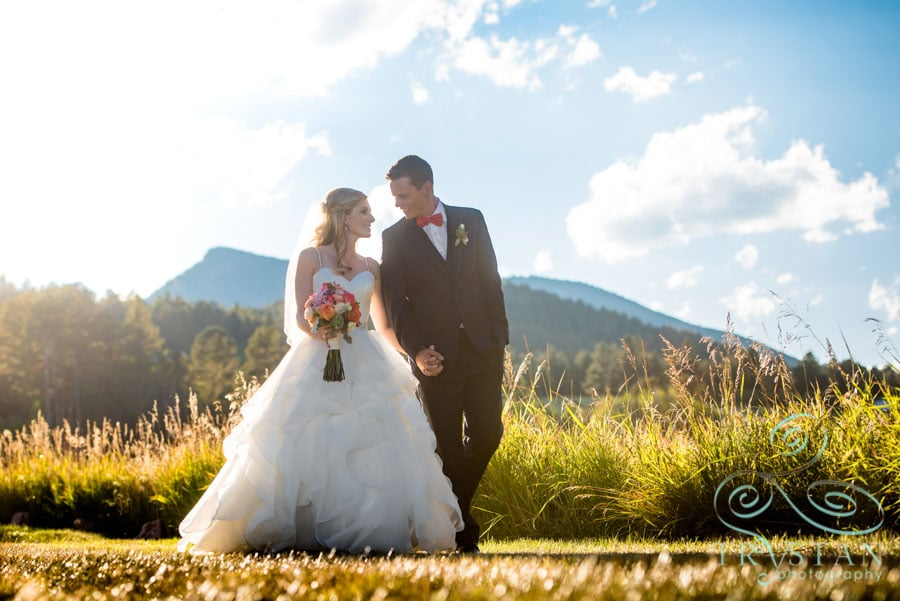 Wedding Photography at Deer Creek Valley Ranch in Colorado - A bride and groom walking together in a field
