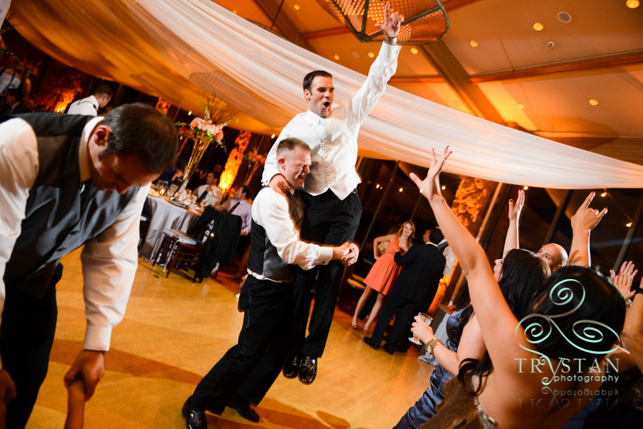 A photograph of a groomsman lifting the groom in the air at the reception and the groom has his hand up and is smiling and yelling in joy.