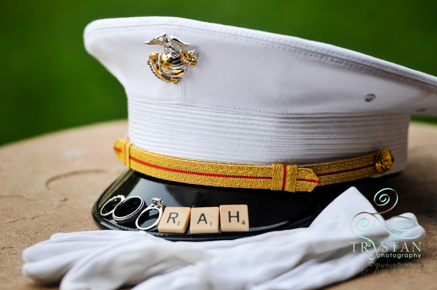"A photograph of a Marine's cover with the wedding rings and scrabble tiles on the brim that spell ""Ooorah""."