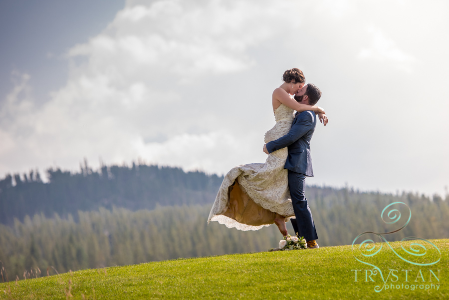 A photograph of a bride and groom passionately embracing with the mountains behind them at their wedding ceremony at Tiger Run in Breckenridge, Colorado.