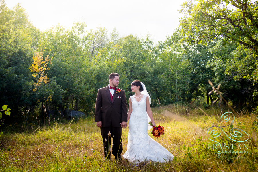 A bride and groom walking through a mountain meadow at Brush Canyon Ranch