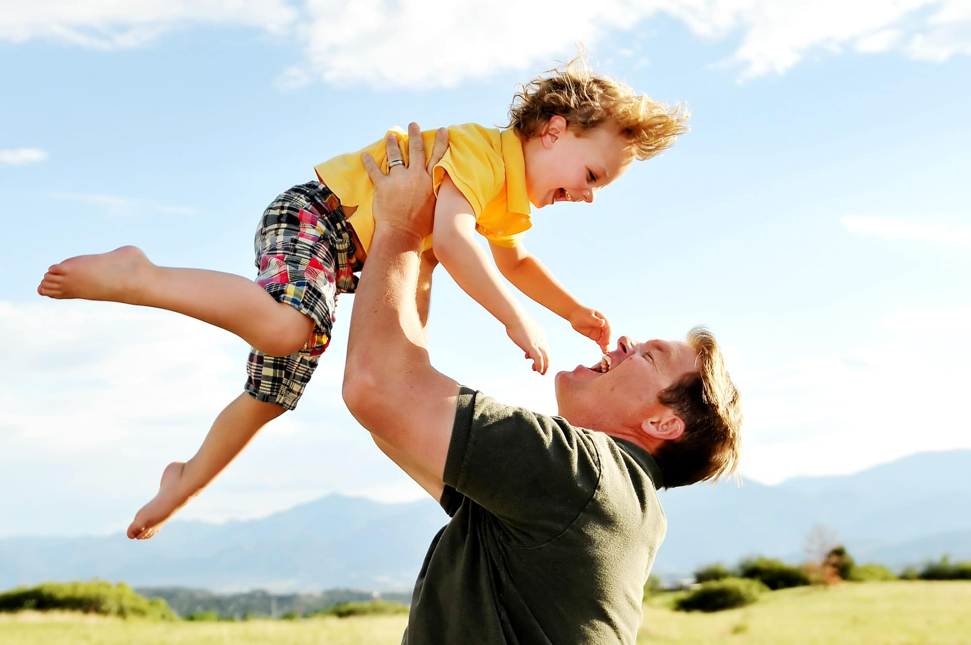 A family portrait of a father lifting his son in the air.