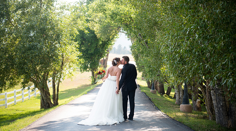 A wedding video still of a couple walking away down a tree-lined lane while holding hands and kissing at The Venue at Crooked Willow Farms.