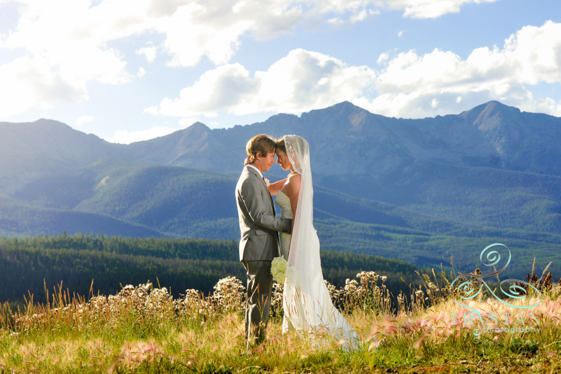 A photography of a couple facing each other and holding each other on top of a mountain at their wedding at Placer Gulch in Breckenridge, Colorado.