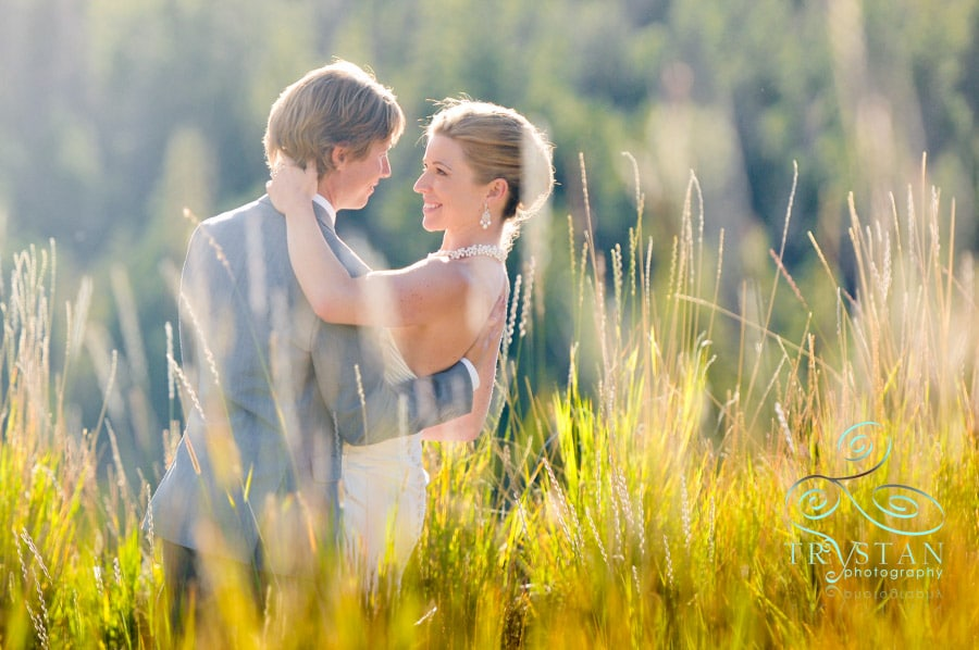 A wedding photograph of a groom carrying a bride in his arms through a Colorado mountain meadow.