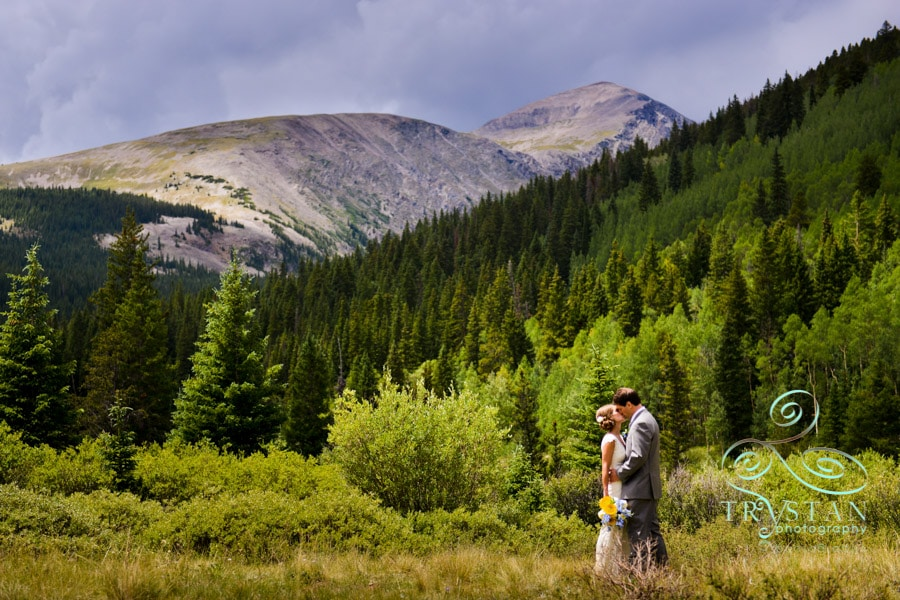 A wedding photograph of a bride and groom kissing in a valley meadow with a mountain peak rising up behind them near Breckenridge, Colorado.