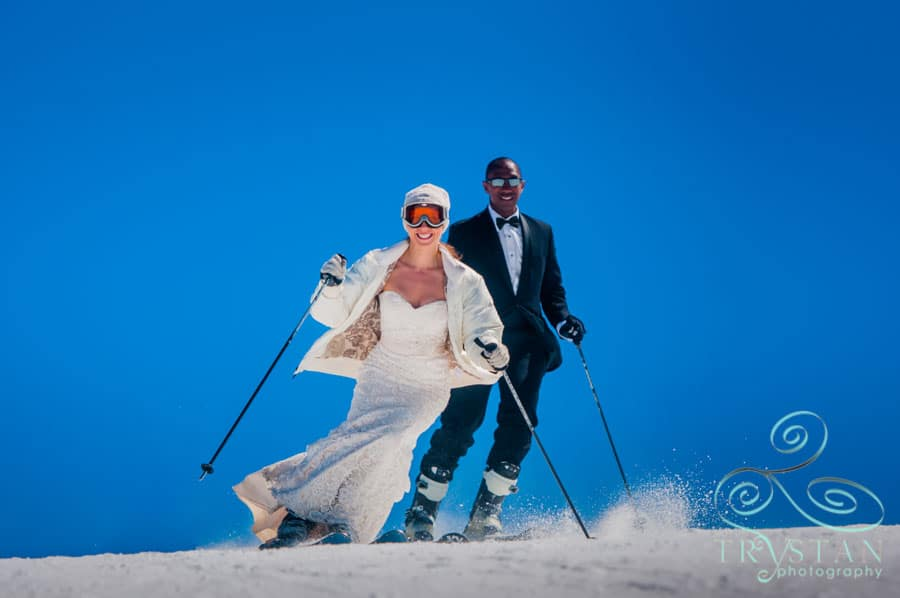 A photograph of a bride and groom skiing in their wedding gown and tuxedo at Keystone Mountain in Colorado.