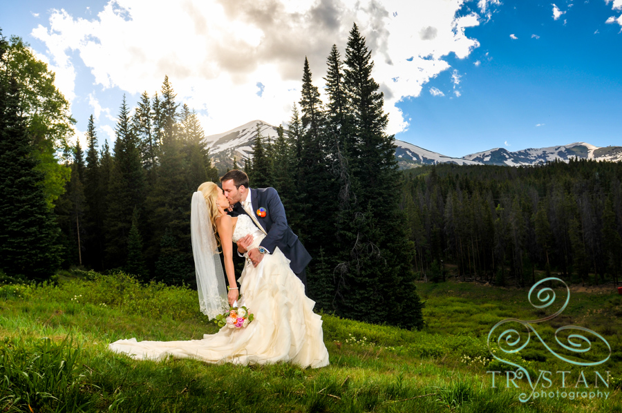 A photograph of a groom kissing and dipping his bride dramatically on a mountainside with Peak 9 looming behind them.