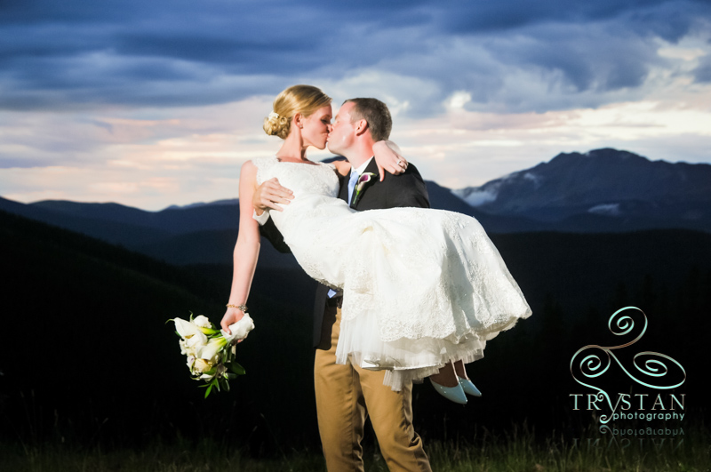 A photograph of a bride being carried in the arms of a groom at dusk on top of Keystone at TImber Ridge with the mountains behind them.