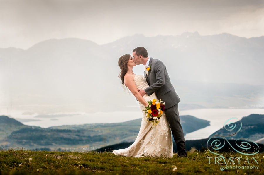 A wedding photograph of a bride and groom kissing at the top of Keystone mountain with Lake Dillon behind.