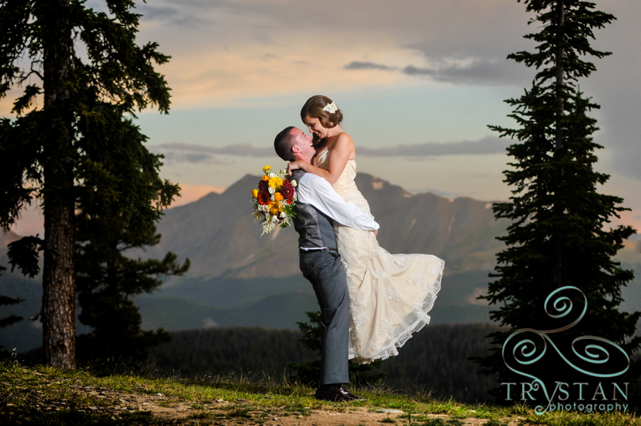 A wedding photograph of a bride being lifted in the arms of a groom at sunset on top of Keystone Resort at Timber Ridge.